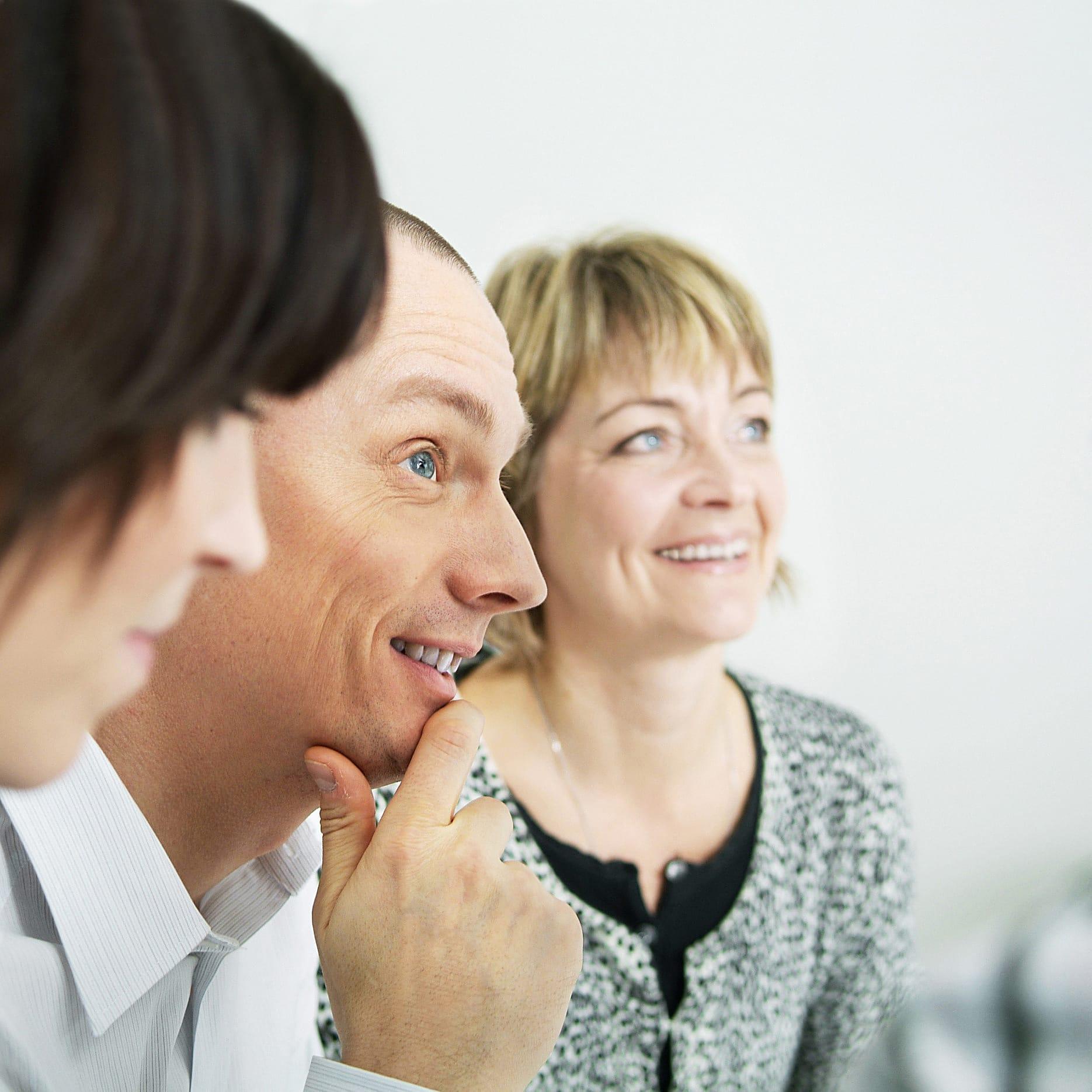 tre personer i profil, tittar glada på någon till höger om bilden.