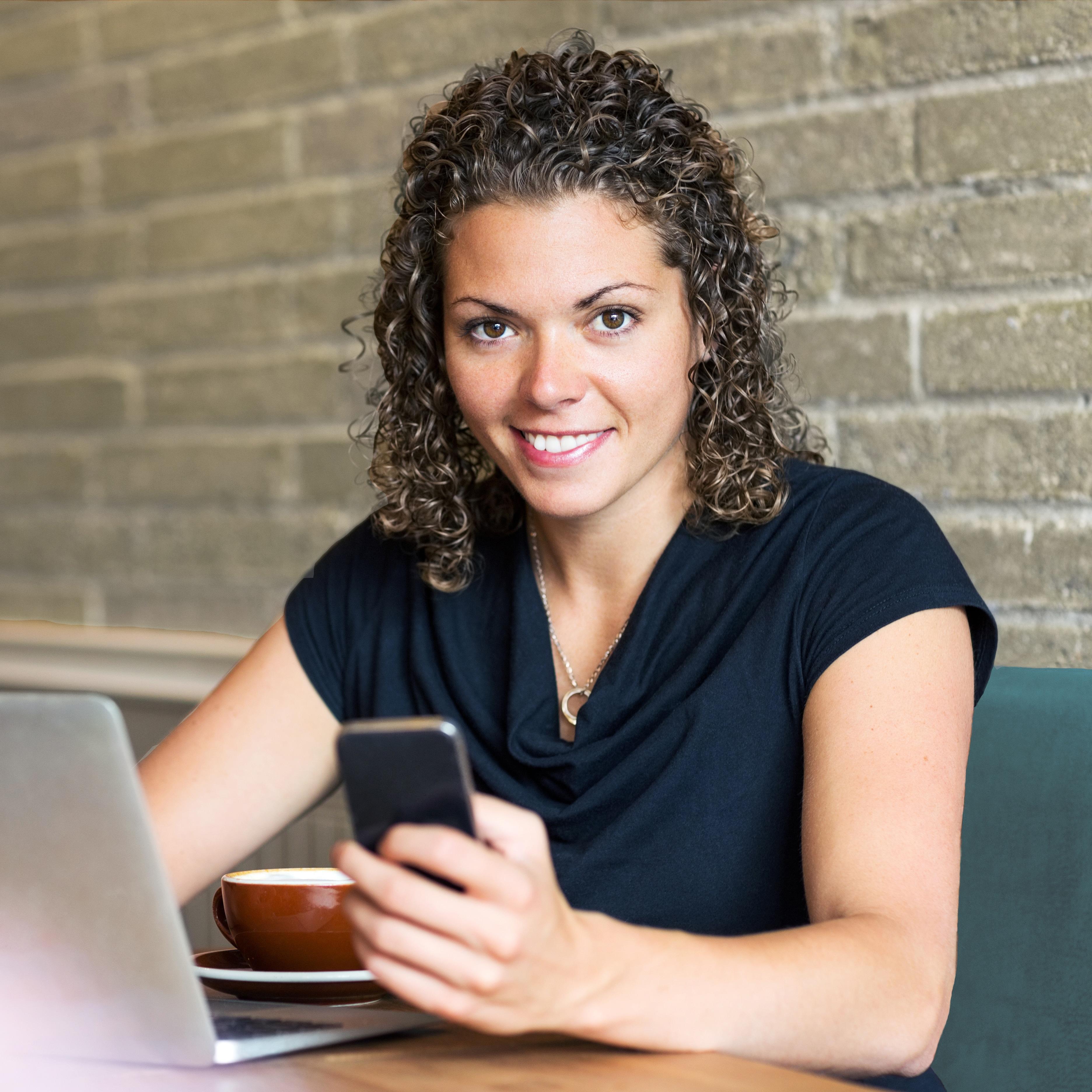 Ung kvinna sitter vid laptop med smatphone i handen.