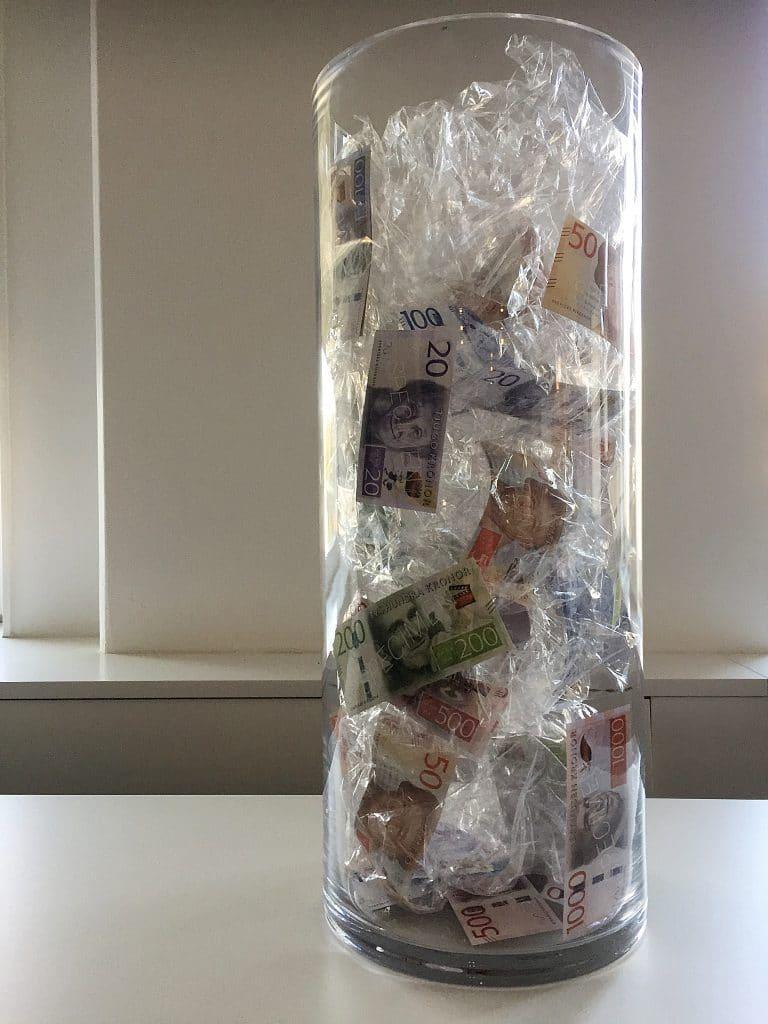 En glascylinder med pengar insmusslade bland genomskinlig plast.