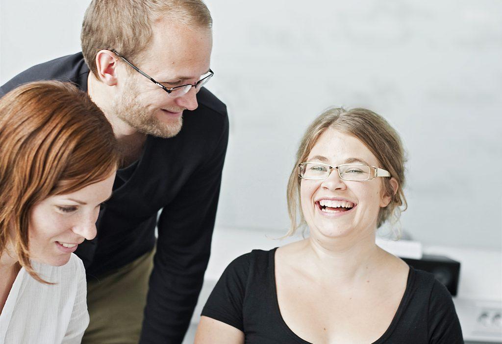 Tre lärarkollegor är glada tillsammans
