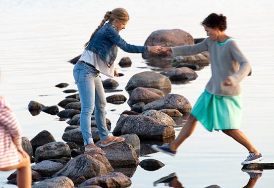 En kvinna hjälper en annan över vattnet.