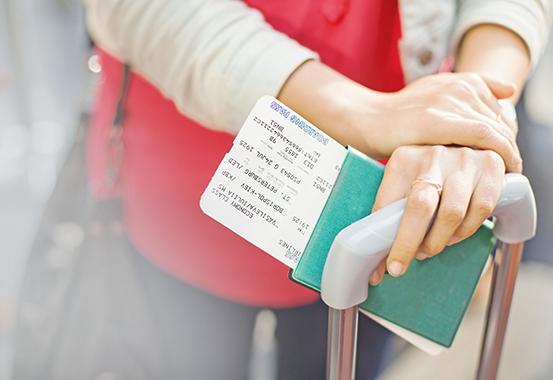 Händer som håller i pass och biljett.
