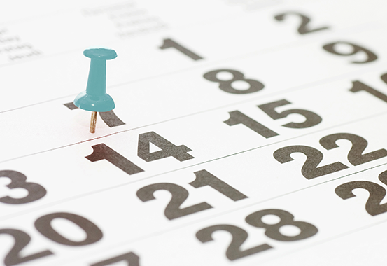 Turkost häftstift som markerar den 14 i ett kalenderblad.